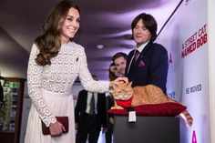 "Catherine, Duchess of Cambridge, Patron of Action on Addiction, greets Bob the cat as she attends the Premiere of ""A Street Cat Named Bob"" in aid of Action On Addiction"