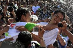 """A Balinese girl, right, tries to avoid a kiss from another during the """"Omed Omedan"""" kissing festival in Bali, Indonesia. Locals believe the festival ensures the good health of those taking part and prevents bad luck hitting the village. During the festival, village priests dump buckets of water over couples to douse their passions."""