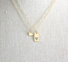 These beautiful, yet simple everyday necklace that will go with everything from your workout clothes to your work clothes.  This listing is for one Mother Daughter set of two (2) gold necklaces consisting of:  *Mother necklace - 18mm rectangle bronze charm with one (1) heart cutout hung on a delicate 18 gold filled flat cable link necklace  *Daughter necklace - petite 7mm bronze heart charm hung on a delicate 18 gold filled flat cable link necklace  This set is also available in sterling…