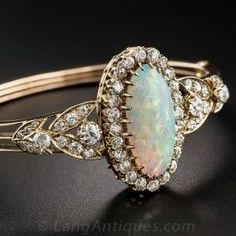 An oval opal, weighing approximately 6.10 carats and displaying an array of kaleidoscopic colors is the central focus of this exceptional Victorian bangle bracelet. The gemstone is securely set in no less than 24 prongs and fills a frame of white old mine-cut diamonds. The centerpiece is embraced on each side by a diamond-set foliate motif leading to a three piece hinged bangle composed of 15K rose gold accented by 3.15 carats total diamond weight. The bracelet fits a 6 3/4 inch wrist size.