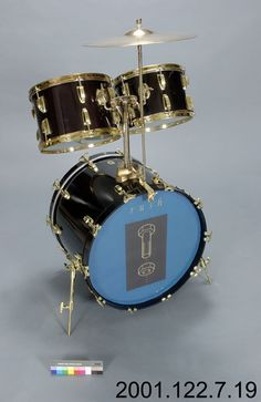 """The bass drum is a structural part of the physical drum set as much as a part of the sound. Displayed is one of Neil Peart's bass drums supporting two rack style Tom Toms with a support mount built into the top of the drum shell, as well as a cymbals stand clamped onto the rim of the drum. Also displayed is the cover from Rush's 1994 album """"Counterparts"""", which the band toured from January until May of the same year. This partial drum kit was likely part of Neil Peart's set-up on that tour."""