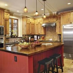 Warm #Kitchen Decor   The standout feature of this kitchen is the central island. Topped with joined planks of antique cypress, the island provides bar seating for informal meals.