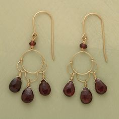 """Artist Thoi Vo forms dainty 14kt gold-filled wire into delicate petals, suspending a faceted garnet droplet from each. A lighter garnet sphere tops the danglers where they meet French wires. Handmade in USA. 1-3/4""""L."""