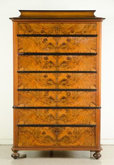"""BIEDERMEIER BURL WALNUT TALL CHEST OF DRAWERS, German, c. 1815-1848, the front featuring a bank of seven large drawers separated by ebonized drawer rails, the molded base raised on bun feet. Dimensions: 62.5""""H x 39.75""""W x 19.5""""D."""