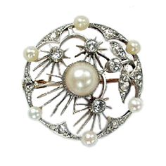 Art Nouveau Edwardian Pearl and Diamond Circular Brooch. C. 1905. This brooch of open-work design is composed of a central single pearl surrounded by a floral motif set throughout with rose cut diamonds, set within a pearl and rose cut diamond border. There are 7 pearls and 26 diamonds in total. All set in 18k white gold.