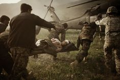 """Moises Saman's Stunning Photos of Humanity in Conflict Zones:  """"Kunar Province, Afghanistan. March 2010. Afghan soldiers carry a wounded comrade into an American medevac helicopter after a Taliban ambush near the village of Tsunek."""""""