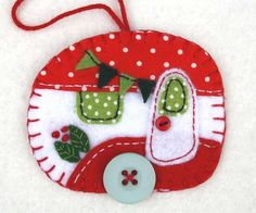 Vintage caravan trailer hanging ornament, handmade from felt and decorated with fabric scraps. With tiny felt bunting and buttons for the wheel and door knob. Colours are red and white with green deta
