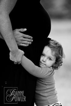 Big sister.. Cute Maternity picture with the dads hands on the moms hip