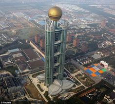 The newly-opened skyscraper in Huaxi Village, Jiangsu province, dwarfs the surrounding buildings It ranks as the 15th-highest skyscraper in the world, standing taller than Paris's Eiffel Tower (324m) and the Chrysler Building (319m) in New York.  It has taken four years for the work to be finished on the 74-storey hotel and residential block at a cost of 3billion yuan