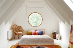 bright attic bedroom with natural light and colorful throw pillows