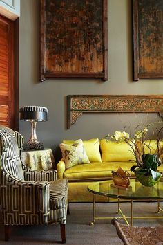 What a stately room: the pattern on the chair, the antique wall art, and the richly colored couch help create one of those rooms that could be found in a multi-generational historic home that screams old money.  Don't you think?
