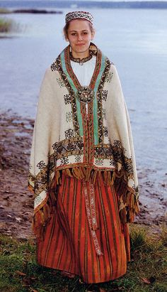 Costume of Selonia or Augšzeme Province, Latvia. This is an old costume from the area around Krustpils. She is wearing an old chemise from Viecpiebalga. This costume falls very much into the east Latvian tradition. Let us look at the various parts of it. The skirt is one of the three types typical of  Augšzeme. If you look closely, you will see pale designs on the orange stripes.