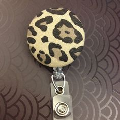 Leopard print fabric covered button badge holder & reel for nursing student uniforms. A very cute way to display your primal meowess! From the SailorBettyShop, priced at $6.00