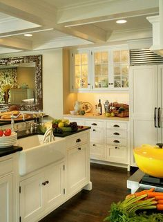 The large farmhouse sink located in the central kitchen island allows the homeowner to keep an eye on the kids while working. The raised center of the island conceals the work area from the eating section. I also love the cupboards