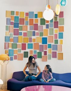 Clémence and daughter Clara, nine, relax on a purple Pierre Paulin 261 sofa below an installation by artist Alan McCollum,, at their home in Paris, France. Photo by Philippe Munda.  Photo by: Philippe Munda