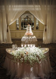 LUSH cascading sweetheart table arrangement in whites and blush with greenery and a cake table backdrop  I Nature of Design with Janet Flowers I Eli Turner Photography