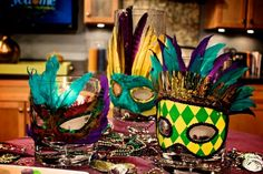 masks on glass vases with beads - great decor for buffet table