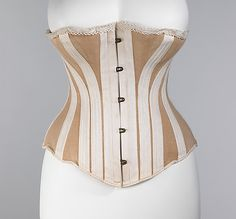 1885 Corset  Culture: American  Medium: cotton, metal, bone  This specific corset appears to be designed for casual and/or active wear due to the choice of fabric. Stretch jersey allows the wearer to move and the locked clasps ensure that the corset will not come undone during activity. Extremely simplistic, the lace trim at top is the only adornment.