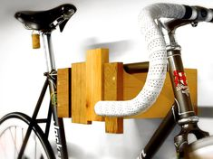 A bike rack that looks good when the bike is out to play. this wall mounted bike rack is made of reclaimed wood and end-cuts, utilizing scrap materials to make something functional. Wood Bike Rack, Wall Mount Bike Rack, Bike Mount, Bike Storage Options, Bike Storage Apartment, Bicycle Hanger, Bicycle Stand, Indoor Bike Rack, Rack Solutions