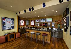 Non-essential add-on: A galley kitchenette. Practice chili cook-offs with an adjoining bar counter where your pals to keep you company while you cook. This sports-themed man cave is a great setup.