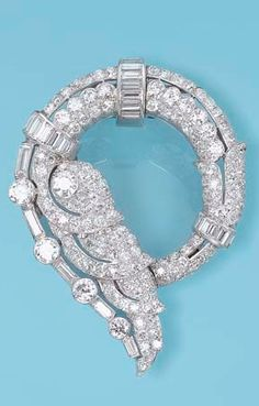 *AN ART DECO DIAMOND BROOCH  Designed as a pavé-set diamond stylised wave with circular and baguette-cut diamond detail, circa 1925, 5.5 cm wide, with French assay marks for gold and platinum.