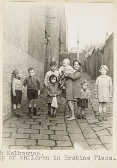 Children in Erskine Place, North Melbourne Australia. Slums. taken by F. Oswald Barnett born in Brunswick, Victoria. A committed Methodist and housing reformer, he led a crusade against Melbourne's inner city slums. In 1936 he was appointed to the Slum Abolition Board and from 1938-1948 he was the vice-chair of the Housing Commission. In this position he attempted to shape compassionate public housing policy.
