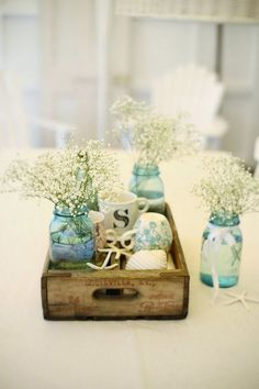Cottage inspired flower arrangement. Smaller flower arrangements are also beautiful when you know how to arrange them right. Take a look at this pretty and compact arrangement of white baby's breath flowers with small cups and sea shells.