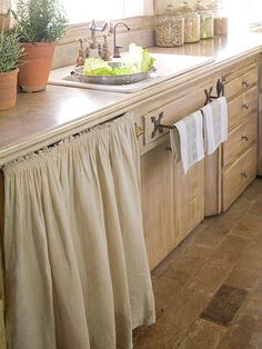 Hide dishwasher with simple curtain rod n burlap material will give that beachy feel
