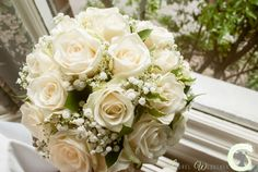 Hand tied bouquet of ivory roses and gypsophila
