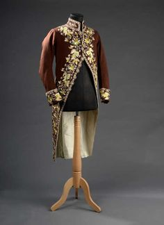 Coat and breeches (habit à la francaise), France, late 18th century. Chocolate brown wool plain weave, lavishely embroidered with floral motifs in polychrome silk, fabric covered and embroidered buttons.