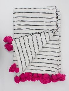 The Scribble Stripe Blanket, a traditionally handwoven Moroccan cotton blanket in cream with abstract black stripe detailing complete with bright tassel pom poms to finish.