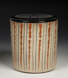 """Mizusashi or water container for Matcha tea ceremony, in a cylindrical form decorated in warabite style on the exterior with orange, brown and blue vertical lines. Of stoneware with a crackled cream glaze, over-decorated in iron oxide brown and orange, with blue gosu. From the Seto Ware kilns. With a black lacquered, fitted lid. Late Edo period, circa 1825 – 1850.  5 ¾"""" high x 5 5/8"""" diameter."""