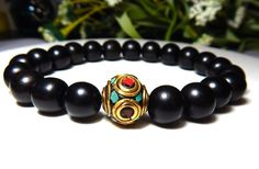 Tibetan Ebony wood mens bracelet made with a 10mm Ebony wood and a 10mm Nepal Bead. Ebony Wood Properties: Associated with positive luck and a balance of energies. Here is a general guide to sizing: W