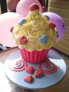 Wilton Giant Cupcake. - Birthday cake for both of my daughters to share.  (One day apart) I BIG thank you to mrsvb78 for the tutorial on the chocolate wrapper.  No problems at all!  Gluten free butter cake mix and buttercream icing with fondant hearts.