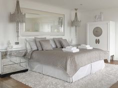 Angmering-On-Sea Beach House Bedroom. White and neutral stylish bedroom interior with mirrored cabinet and chandelier.