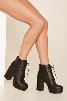 A pair of faux leather booties featuring a tall platform, a chunky block heel, and a lace-up top.