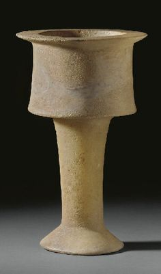 A BACTRIAN ALABASTER CHALICE  CIRCA LATE 3RD-EARLY 2ND MILLENNIUM B.C.  With a tall stem on a conical foot, the cylindrical bowl tapering slightly towards the wide disk rim  13¾ in. (34.9 cm.) high