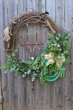 Weidenkranz mit Harken, Gartenschlauch und Grün dekoriern