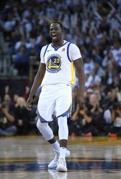 Draymond Green of the Golden State Warriors reacts after making a threepoint shot against the Cleveland Cavaliers during an NBA basketball game at...