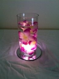 These were super inexpensive  quick to make. The glass vases, mirrors and flowers were all purchased from the Dollar Tree for $1 each. The flowers actually came off a Hawaiian Lei that was took apart. And the lighting is a submersible led light. Just place the light in the vase, add water and then place the flowers in the water.