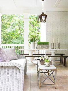 A coffee table invites kicking back on this vintage inspired porch. Midwest Living