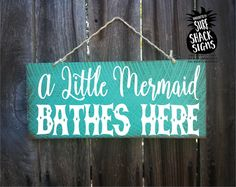 A Little Mermaid Bathes Here sign. Measures 18 wide x 8 tall. Hand painted with a distressed beach look. Jute Twine hanger on top. Great for