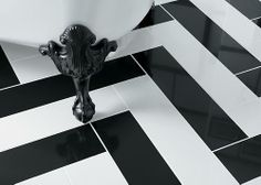 With black and white from the chevron floor to the wall tile, this black and white bathroom has a modern yet classic flair. It features a claw-foot bath, and black vanity with vanity top.and vintage-inspired faucet. Chevron Tile, Chevron Floor, Charlie Chaplin, Claw Foot Bath, Cast Iron Bath, Black White Bathrooms, Bathroom Gallery, Bathroom Wallpaper, Floor Patterns