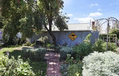 Aldona's gorgeous back garden, with brick pathways built using recycled bricks from the empty block of land next door. The old kangaroo road sign is from the Sunday Market in Ballarat. Photo – Eve Wilson, production – Lucy Feagins / The Design Files.