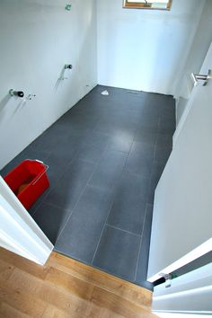 Charcoal grey large rectangular bathroom floor tile with dark grout - see the tiling process so you know what to expect!
