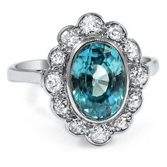 The Genista Ring A gorgeous oval shaped blue zircon truly stands out in a bezel setting. A halo of round diamond accents held in scalloped frames encircle the center gem. A smooth 17 karat white gold band finishes off the look (approx. 0.45 ct. tw.). $2805