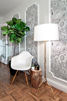 Used as panels on the wall, malachite wallpaper injects the space with a hint of glamour without the hassle of wall-to-wall installation. A stump end table, fiddle leaf fig tree and gold floor lamp offer natural texture and form, while the molded armchair is all modern.