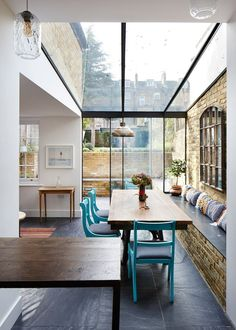 Dining Room decor ideas - modern rustic contemporary style with wood table, turquoise painted wood chairs, bench seating against a brick wall and slate floors. Refurbished and extended Victorian property in east London