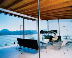 Loredana Dall' Amico reads in the living room, where all the seating was designed by her husband. The floating stainless steel unit behind her is also his design and contains a state-of-the-art stereo system.  #dwell #lakesideliving #outdoorlivingroom