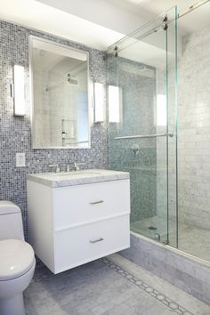 This luxe modern bathroom was created for a New York Greenwich Village Apartment. It features custom tile work and a refreshing palette of gray and white.